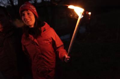 Frau in der Dunkelheit mit Fackel in der Hand. (© Rothaarsteigverein e.V.  Tatonka)