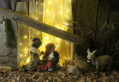 Biblische Erzaehlfiguren zeigen Maria und Josef im Stall auf dem Boden sitzend. Maria hat das Kind im Arm. Daneben steht ein Esel und frisst Heu.. (© Doerflicher Adventsweg Breitenberg)