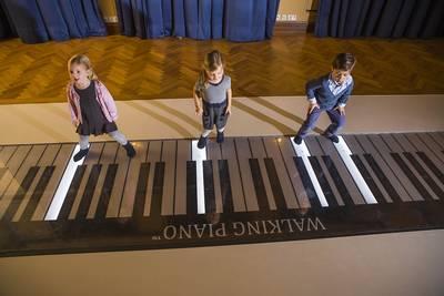 Kinder auf dem Walking PianoMichael Bode. (© LAUF DEIN LIED! Familienworkshop im TOCCARION)